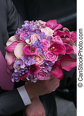 wedding bouquet for bride in hands of groom