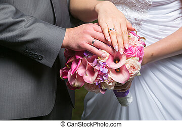 hands of bride and groom on wedding bouquet - hands of bride...
