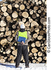 Forester with folder an opposite logs off the pile