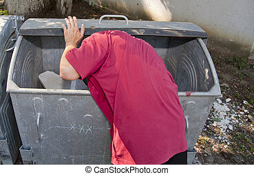 young man in dumpster - young man looking in a dirty...