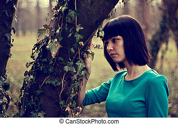 Beautiful girl in a green dress in the fairy forest -...
