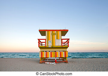 Summer scene in Miami Beach Florida, with a colorful lifeguard house in a typical Art Deco architecture, at sunset with ocean and sky in the background.