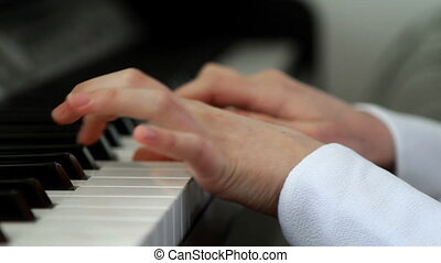 Girl`s hands playing at piano