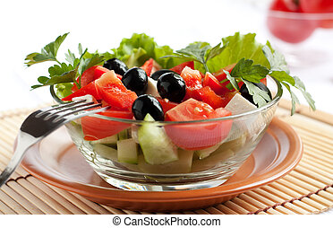 Juicy Greek salad in  glass salad bowl.