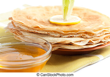 Fresh pancakes on a plate with honey