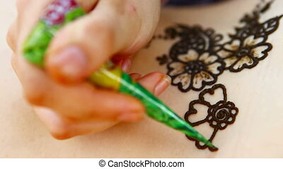 Drawing a henna on a body. Two stages