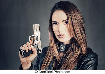 woman holding up her gun - beautiful woman holding up her...