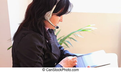 adult woman with headset talking on the phone and typing on...