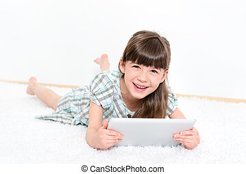 Joyful little girl with a tablet - Joyful pretty little girl...