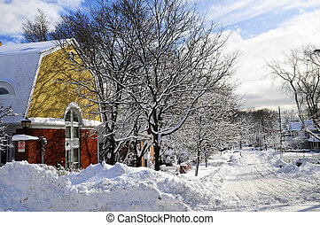 Winter street with lots of snow and colorful houses in...