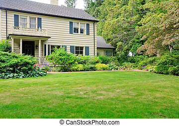 Large brown house exterior with summer garden.