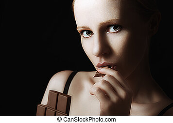 sexy beautiful young woman eating chocolate on a dark...