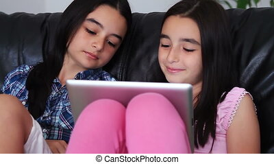 teenage girls having fun on tablet - Two happy teenage girls...