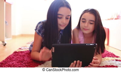 Two teenage girls using tablet pc - Two happy teenage girls...