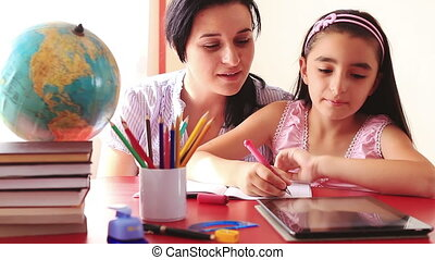 Mother and daughter doing homework on tablet pc
