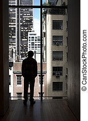 A man looking out of her window - A man with hands in pocket...