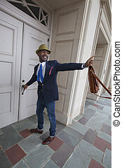 Opening a door and waving - A fashionable young African...