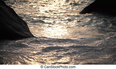 A water flows between two rocks in the sea at sunset