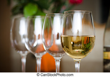 Wine glasses - A wine glass with wine and 3 empty ones with...