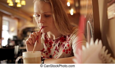 Girl is drinking coffee latte in cafe.