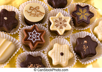 Cute christmas chocolates on gold background
