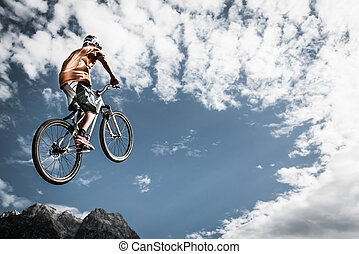 young boy jumps high with his bike in front of mountains and...