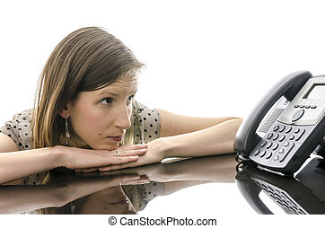 Woman waiting for a phone call while looking at telephone...