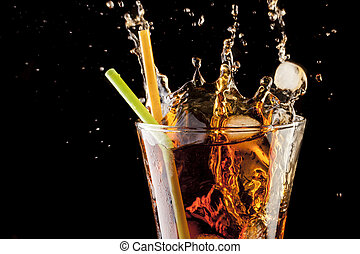 fresh cola juice and ice cubes splash in a glass on black...