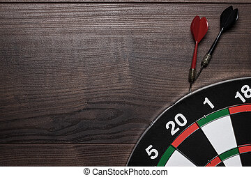 target and two darts over brown wooden table background -...