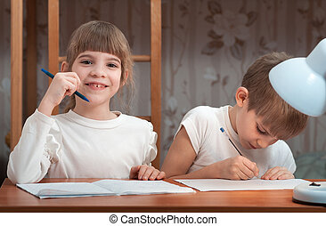 children do their homework at the table