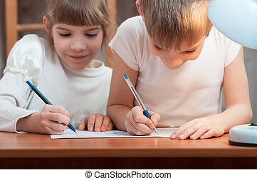 children draw at the table in the lamplight