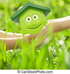 Eco cartoon house in hands against spring green background...