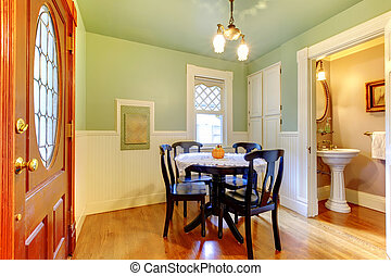 Green antique casual dining room with black table.