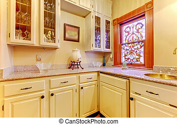 White kitchen pantry with antique cabinets and window