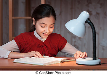 girl at desk reading a book by light of lamp