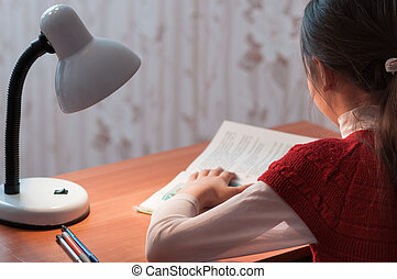 girl at desk reading a book by light of the lamp - the girl...