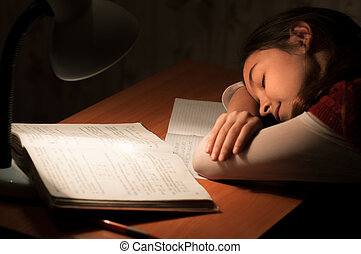 Girl asleep at a table doing homework by the light of the...