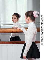 girl standing at barre and looks through mirror - a...