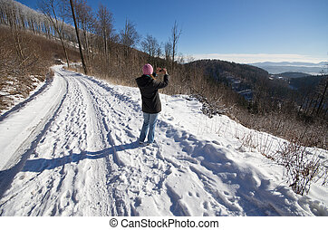 Woman taking photo during the winter