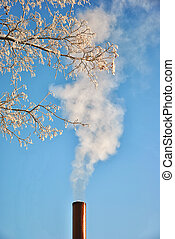 Factory pipe with smoke over blue sky background
