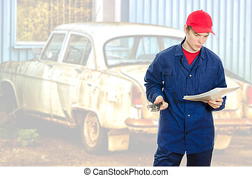 Young handyman reading manual over old car background