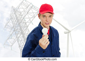 Young electrician in uniform with bulb on transmission tower background