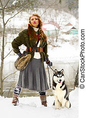 Happy young woman standing with siberian husky dog in winter...