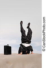Head in sand stand - Businessman standing on his head with...