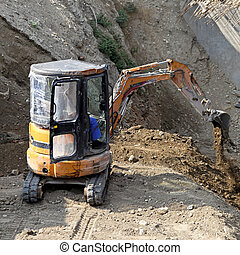 Mini excavator digging earth at construction site