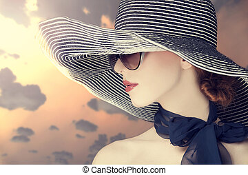 Fashion women in wide hat at sunrise