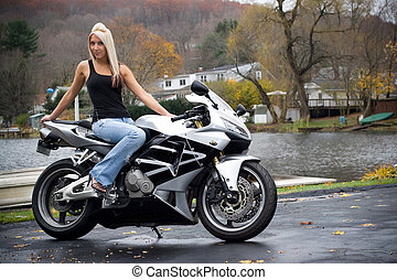 Blonde Biker Girl - A pretty blonde girl posing on a...
