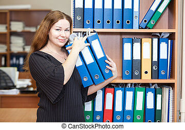 Smiling business woman arranging documents with folders