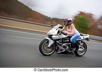 Blonde Biker Girl - A pretty blonde girl in action driving a...