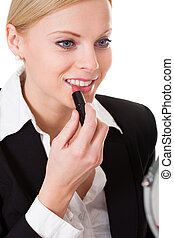 Attractive businesswoman applying lipstick. Isolated on...